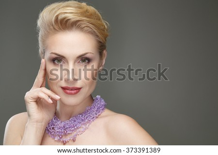 Dressed to impress. Attractive mature woman smiling to the camera looking confident touching her face copyspace on the side - stock photo