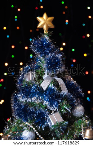 dressed up fur-tree with the star on the top of his head on a black background with colored lights
