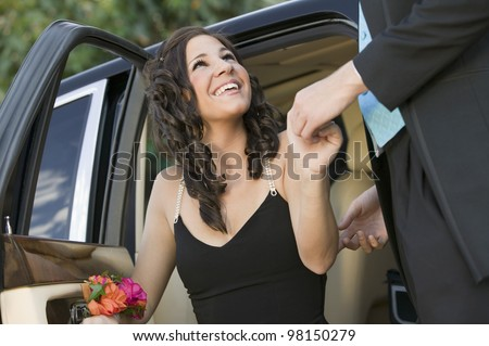 Dressed Up Girl Being Helped From Limo - stock photo