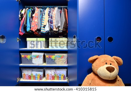 Dressing Closet For Kids With Clothes Arranged On Hangers And Teddy  Bears.Colorful Wardrobe Of