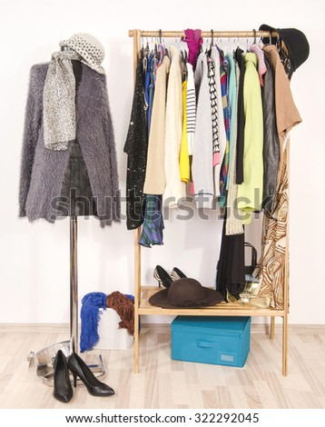 Dressing closet with autumn clothes and accessories. Tailor's dummy wearing a fluffy grey sweater with scarf and hat. - stock photo