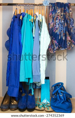 Dressing closet with blue clothes arranged on hangers - stock photo