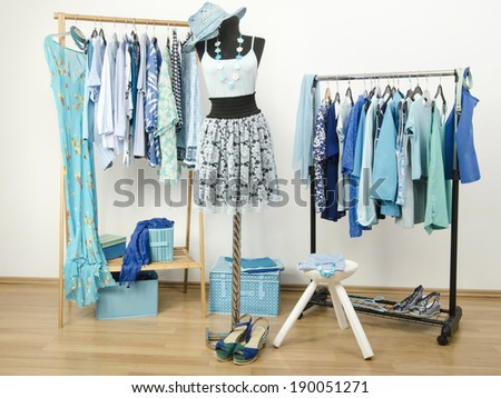 Dressing closet with blue clothes arranged on hangers and an outfit on a mannequin. Wardrobe full of all shades of blue clothes, shoes and accessories. - stock photo