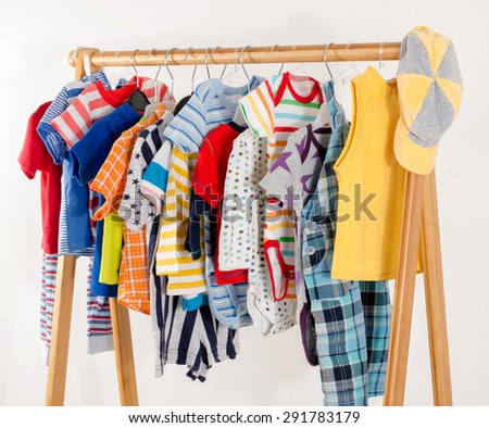 Dressing closet with clothes arranged on hangers.Colorful wardrobe of newborn,kids, toddlers, babies full of all clothes.Many t-shirts,pants, shirts,blouses,yellow hat, onesie hanging - stock photo