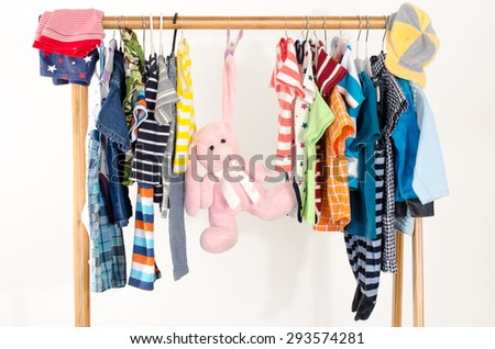 Dressing closet with clothes arranged on hangers.Colorful wardrobe of newborn,kids, toddlers, babies full of all clothes.Many t-shirts,pants, shirts,blouses, onesie on a rack, pink rabbit toy hanging - stock photo