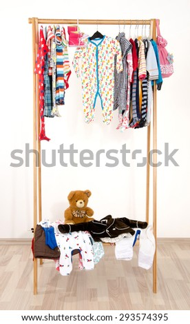 Dressing closet with clothes arranged on hangers.Colorful wardrobe of newborn,kids, toddlers, babies on a rack.Many t-shirts,pants, shirts,blouses, onesie hanging. Messy clothes thrown on a shelf - stock photo