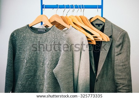 Dressing closet with clothes arranged on hangers. Fashion and shopping concept. Toned picture