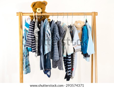 Dressing closet with clothes arranged on hangers.Wardrobe of newborn,kids, toddlers, babies full of all clothes.Many t-shirts,pants, shirts,blouses, onesie on a rack, bear toy hanging - stock photo