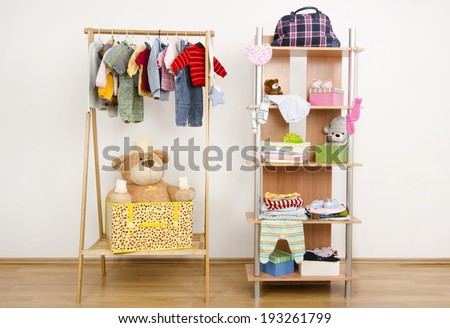 Dressing closet with complementary clothes arranged on hangers.Wardrobe of newborn,kids, babies full of all shades of blue an orange clothes, shoes,accessories and toys - stock photo