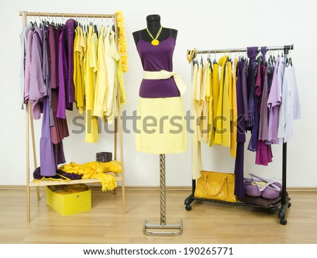 Dressing closet with complementary colors purple and yellow clothes arranged on hangers and an outfit on a mannequin. Wardrobe with violet and yellow clothes and accessories. - stock photo