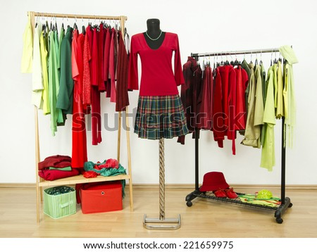 Dressing closet with complementary colors red and green clothes arranged on hangers and a plaid outfit on a mannequin. Wardrobe full of all shades of green and red clothes and accessories. - stock photo