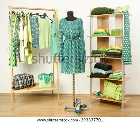 Dressing closet with green clothes arranged on hangers and shelf, dress on a mannequin. Wardrobe full of all shades of green clothes and accessories. - stock photo