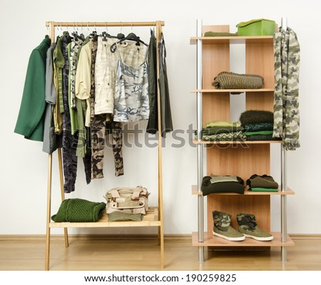 Dressing closet with military camouflage khaki green clothes arranged on hangers and shelf.  Wardrobe with camo pattern clothes, shoes and accessories. - stock photo