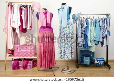 Dressing closet with pink and blue clothes arranged on hangers with outfit on two mannequins. Wardrobe full of all shades of blue and pink clothes, shoes and accessories. - stock photo