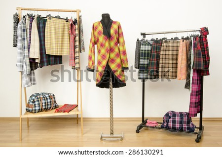 Dressing closet with plaid clothes arranged on hangers and a jacket on a mannequin. Colorful wardrobe with tartan clothes and accessories. - stock photo