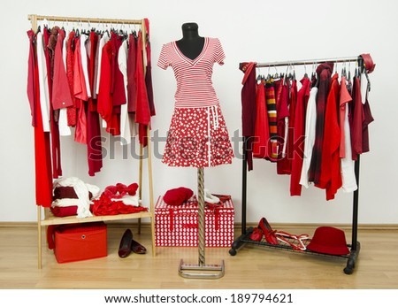 Dressing closet with red and white clothes arranged on hangers and an outfit on a mannequin. Wardrobe full of all shades of red clothes, shoes and accessories. - stock photo