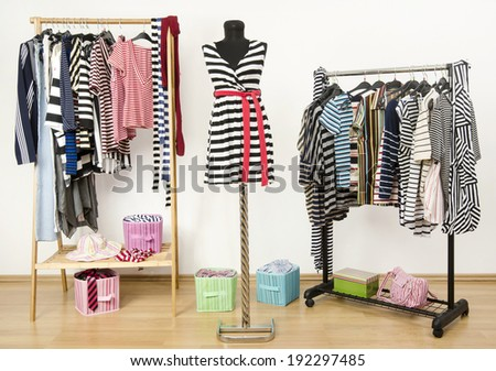 Dressing closet with striped clothes arranged on hangers and a  black and white outfit on a mannequin.  Colorful wardrobe full of clothes and accessories with stripes pattern.