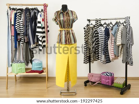 Dressing closet with striped clothes arranged on hangers and an outfit on a mannequin.  Colorful wardrobe full of clothes and accessories with stripes pattern. - stock photo