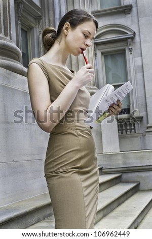 Dressing formally and a pen touching lips a professional business woman is working outside an office building, reading, writing and thinking/Working Outside - stock photo