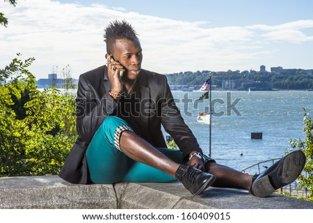 Dressing in a black blazer, green pants and leather shoes, a young black guy with mohawk hair is sitting by a river, talking on the phone. - stock photo