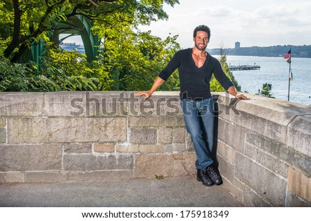 Dressing in a black sweater,  blue jeans and leather shoes, a handsome, sexy, middle age guy with mustache and beard is leaning on a half wall fence by a river, smilingly looking at you. / Traveler  - stock photo