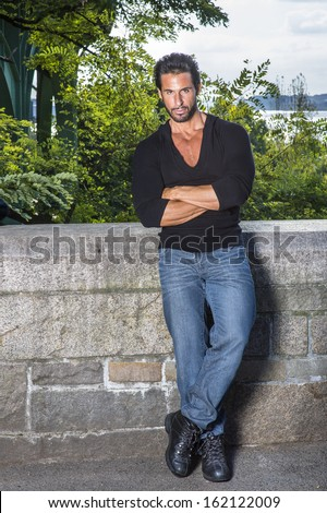 Dressing in a black sweater, blue jeans and leather shoes, crossing arms, a handsome, sexy, middle age guy with mustache and beard is leaning against the half wall fence, seriously looking at you. - stock photo