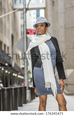 Dressing in a black woolen cropped jacket,  a gray fitted dress, a long white scarf around her neck, wearing a woolen Gangster Fedora hat, a young black woman is standing on street. / Street Fashion