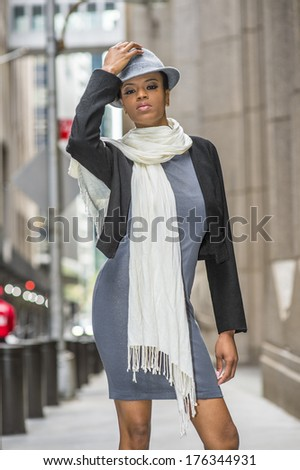 Dressing in a black woolen cropped jacket,  a gray fitted dress and a long white scarf around her neck,  a black woman is standing on the street, wearing a woolen Gangster Fedora hat. / Street Fashion - stock photo