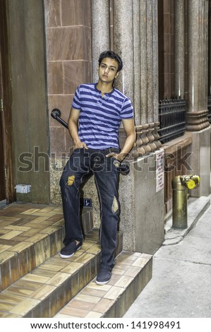 Dressing in a blue lines T shirt, a fashionable pants, a young asian teenager is leaning on a doorway and into deeply thinking./Thinking outside - stock photo