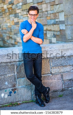 Dressing in a blue long sleeves with roll-tab Henley shirt, black jeans, leather sneakers, glasses and a wristwatch, crossing arms and one hand touching his chin,  a young guy is relaxing outside. - stock photo