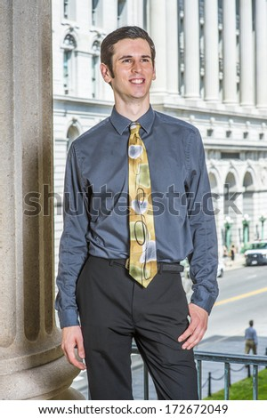 Dressing in a blue shirt, black pants, a colorful tie, a young college student is standing outside a business building, smilingly looking forward. / Portrait of College Student