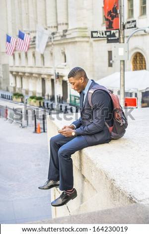 Dressing in a blue suit and leather shoes, caring a backpack, a young black businessman is sitting outside to check messages on his mobile phone. There is a Wall Street sign in the background. / Text  - stock photo