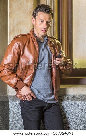 Dressing in a brown leather jacket, black pants, holding a mobile phone, a young handsome guy is standing by a window, opening his mouth and talking to you. / Speaking to You - stock photo