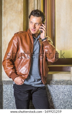 Dressing in a brown leather jacket, gray shirt and black pants, one hand putting in a pocket,  a young handsome guy is standing by a small window, making a phone call. / Making Phone Call  - stock photo