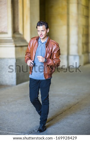 Dressing in a brown leather jacket, gray undershirt, black pants, one hand holding a cell phone,  a young handsome guy is walking and passing by a business building. / Walking - stock photo