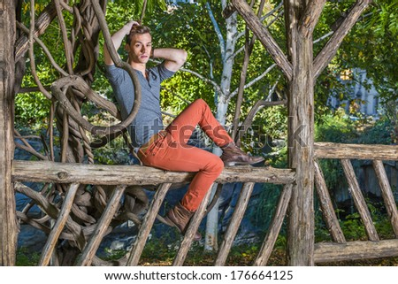 Dressing in a gray Henley shirt, red jeans, boot shoes, a young guy is sitting on a wooden fence, two hands managing his hair, relaxing outside. / Relaxing in Park