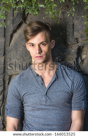 Dressing in a gray long sleeves with roll-tab Henley shirt, a young handsome guy is standing by rocks, green leaves on the top,  and charmingly looking at you. / Portrait of Young Handsome Guy  - stock photo