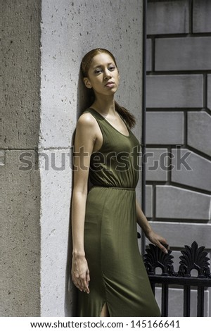 Dressing in a green Tank Dress, a young black girl is lean on wall and  thoughtfully looking at you. /Thinking Outside - stock photo