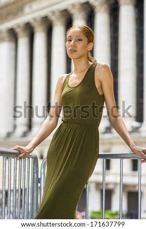 Dressing in a green Tank Dress, narrowing eyes and tired,  a young black girl is standing in the front of office buildings to take a break. / Relaxing Outside