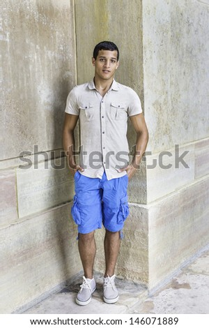 Dressing in a iron short sleeve shirt, blue shorts, a young attractive guy is standing in the corner of walls and looking at you. /Portrait of Young Guy