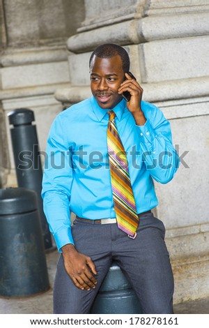 Dressing in a light blue shirt, a colorful pattern tie, gray pants, a young black businessman is smiling, sitting outside to make a phone call on his mobile phone. / Calling Outside