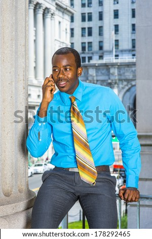 Dressing in a light blue shirt, gray pants,  a pattern tie, a young black businessman is sitting outside an office building, making a phone call. / Calling Outside
