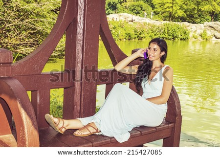 Dressing in a light blue, v neck, long dress, wearing  brown sandals, a young sexy woman with long curly hair is sitting on a red, long bench chair by a lake, smiling, talking on a mobile phone. - stock photo