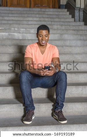 Dressing in a light orange short sleeve V neck shirt, jeans, a young handsome black student is sitting on stairs outside an office building, checking messages on his mobile phone. / Text - stock photo