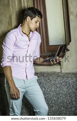 Dressing in a light pink shirt, light green pants,  a young handsome guy is standing by a window and looking at a small computer./Study Outside - stock photo