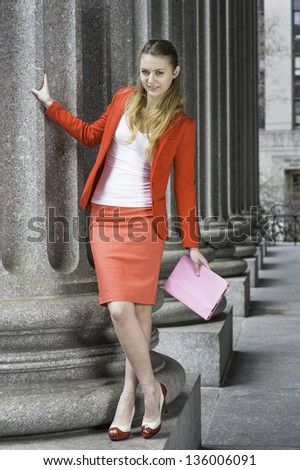 Dressing in a red blazer, a light red skirt, fashionable shoes, a young student is cheerfully standing on a base of a pillar./Portrait of Young Student - stock photo