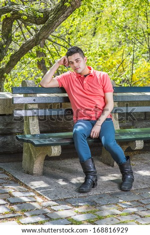 Dressing in a red Polo shirt, green pants and long leather boots, one arm supporting his head, a young handsome guy is sitting on a long chair  in the morning of a spring season, relaxing