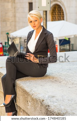 Dressing in a white underwear,  black suit, a young pretty blonde businesswoman is working on a laptop computer outside / Working Outside