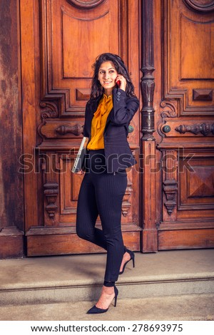 Dressing in black blazer, orange shirt, pants, heels, a young East Indian American business woman walking down vintage style office door way, carrying laptop computer, making call on her mobile phone. - stock photo