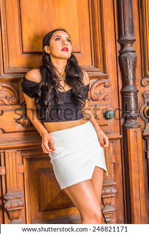Dressing in black, short sleeve top, white short fit skirt, a young student with long curly hair is leaning on library door, looking up, thinking. Concept of teenagers questioning life, self esteem.  - stock photo